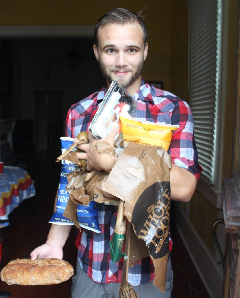 Man smiles with wet paper bag that didn't hold groceries