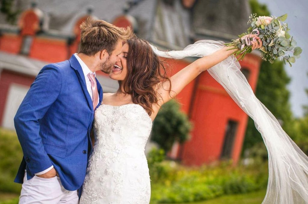 Bride and Groom share a kiss in front of their Swedish Castle on their Wedding Day