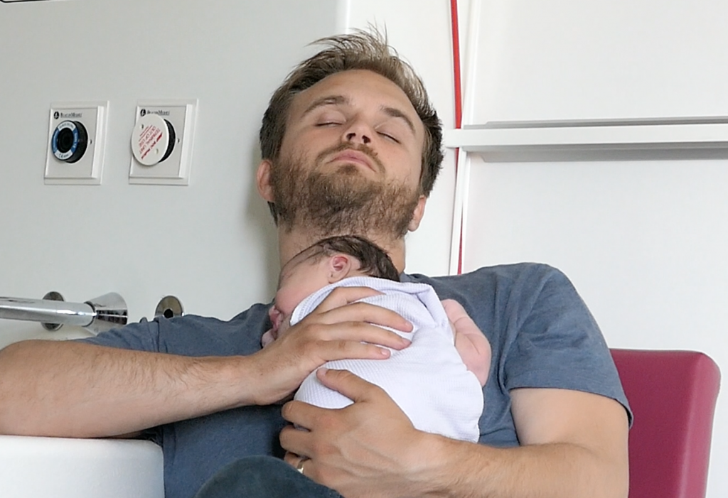 Dad rests with newborn baby on his chest